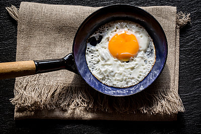 Fried egg in pan and tablecloth - p300m981579f by Sandra Rösch