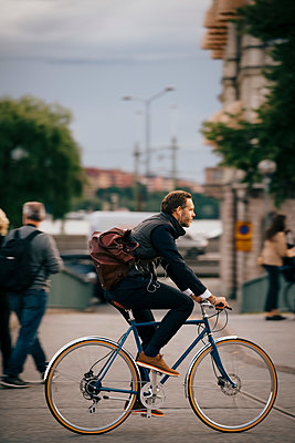 Side view of confident businessman riding bicycle on street in city - p426m2145589 by Maskot