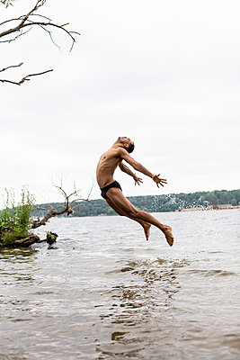 Young man splashes around in bathing lake - p975m2195434 by Hayden Verry