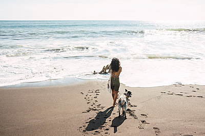 Woman taking pictures on the beach, with her dog. Photographer concept. - p1166m2255547 by Cavan Images