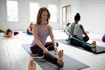 Women practicing yoga with strap in yoga class - p1192m1583343 by Hero Images