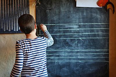 School boy writing on a blackboard - p1519m2260258 by Soany Guigand