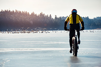 Man cycling on a frozen lake - p312m1147609 by Hans Berggren