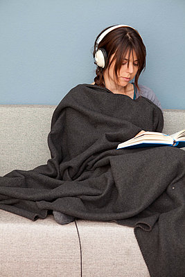 Woman with headphones and book at home - p4540870 by Lubitz + Dorner