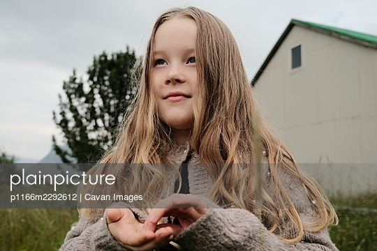 Dreamy girl on gray day in countryside - p1166m2292612 by Cavan Images