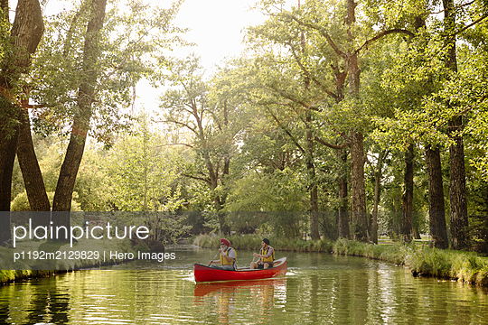 Mature Indian man and son canoeing on lake - p1192m2129829 by Hero Images