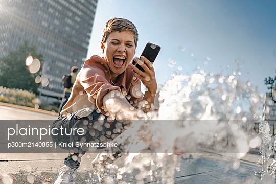plainpicture - plainpicture p300m2140855 - Excited woman at a fountain... - DEEPOL by plainpicture/Kniel Synnatzschke