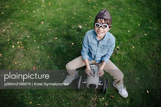 Little boy having fun, riding vintage toy car in the garden - p300m2166679 by Kniel Synnatzschke