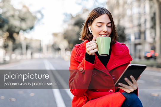 Smiling young woman in winter jacket having coffee while using digital tablet on road - p300m2242896 by COROIMAGE