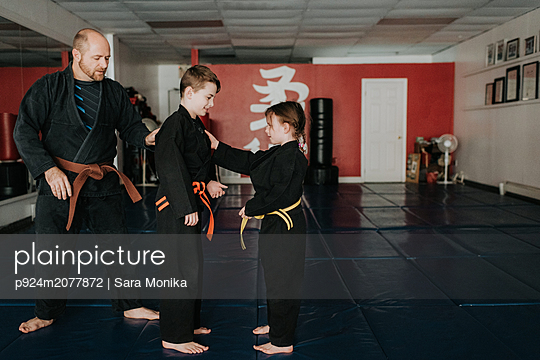 Coach and students practising martial arts in studio - p924m2077872 by Sara Monika