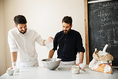 Two bakers standing at a table, preparing bread dough, baking ingredients and a blackboard on the wall. - p1100m1158380 by Mint Images