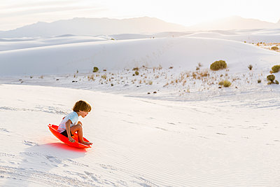 A young boy sledding down white sand dunes - p1100m2164780 by Mint Images