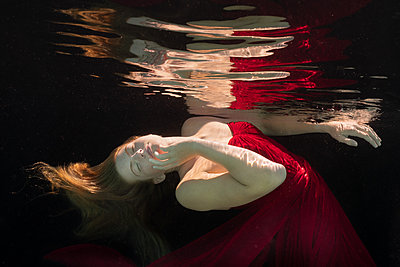 Woman in red dress under water - p1554m2272595 by Tina Gutierrez