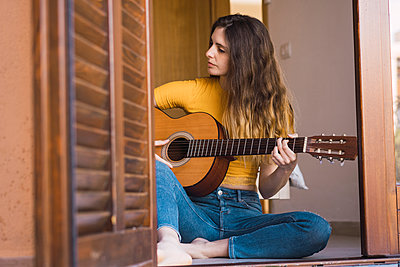 Young woman sitting on the floor at home playing guitar - p300m1581581 von Kike Arnaiz