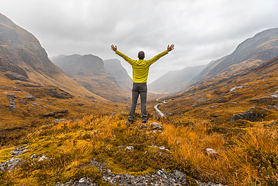 UK, Scotland, man in the Scottish highlands near Glencoe with a view on the Three Sisters - p300m2013245 by William Perugini