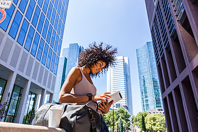 Germany, Frankfurt, young woman with travelling bag and coffee to go using tablet in the city - p300m2030291 von Tom Chance