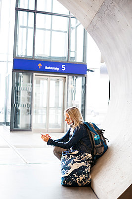 Woman using cell phone at the station - p300m2103063 von Epiximages