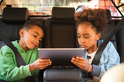 Siblings sharing digital tablet while sitting in electric car - p426m2072356 by Maskot