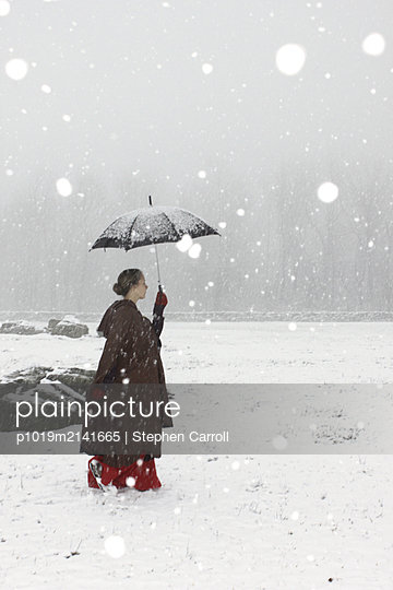 Frau mit Regenschirm im Schnee - p1019m2141665 von Stephen Carroll