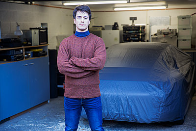 Portrait confident man standing in front of covered car in garage - p1023m2073951 by Tom Merton