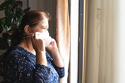 Woman in home during quarantine looking the outside throughthe window - p1166m2214567 by Cavan Images