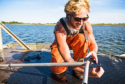 Young man working on the water in aquaculture oyster farm maintenance - p1166m2268897 by Cavan Images