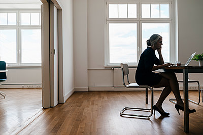 Businesswoman working on laptop in office - p300m1469738 by Kniel Synnatzschke