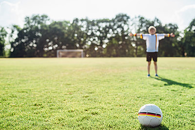 Boy with outstretched arms standing on soccer field between German soccer ball and goal - p300m2005475 von Jana Mänz