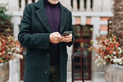 Man in jacket using mobile phone - p300m2273843 by Daniel González