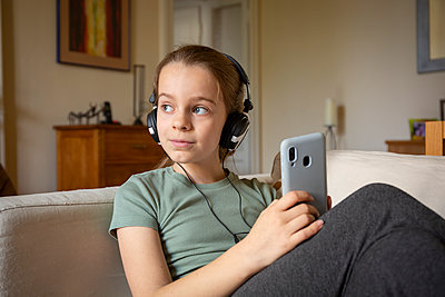 Girl wearing headphones sitting on sofa, holding mobile phone. - p429m2200776 by OPIFICIO 42