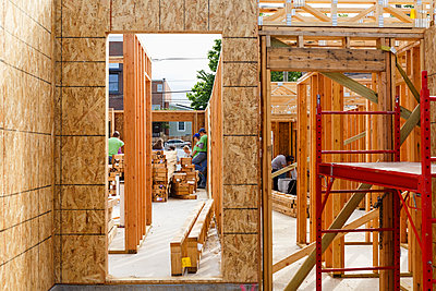 Distant volunteers building house - p555m1522803 by Roberto Westbrook