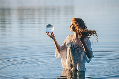 Young woman with long red hair standing in lake gazing at crystal ball - p924m1054057f by Pete Saloutos