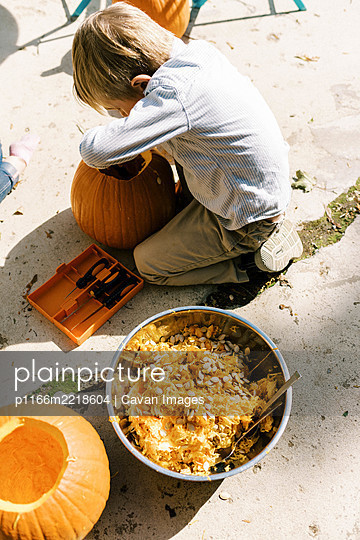 A little boy scooping out his pumpkin for halloween on the patio - p1166m2218604 by Cavan Images