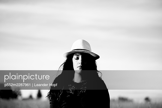 Portrait of black-haired woman with straw hat - p552m2287961 by Leander Hopf