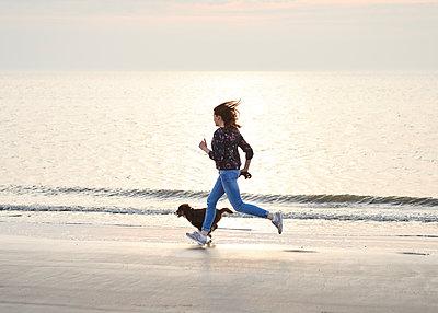 Frau rennt mit Hund am Strand - p1124m1223979 von Willing-Holtz