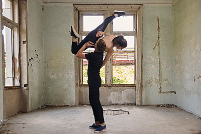 Man lifting ballerina while dancing in old building - p1166m2024701 by Cavan Images