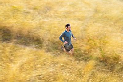 Man runs through tall grass on Bear Canyon Trail in Boulder, Colorado - p1166m2137873 by Cavan Images