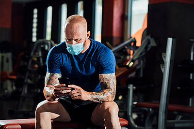 Man wearing face mask using mobile phone while sitting in gym during COVID-19 - p300m2243282 by Miguel Frias