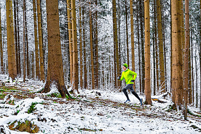 Young male sportsperson jogging in snowy weather at forest - p300m2257284 by Stefan Schurr