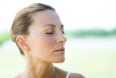 Woman closing eyes - p624m1487338 by Frederic Cirou