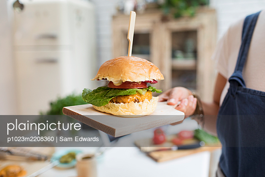 Close up woman holding cheeseburger on cutting board - p1023m2208360 by Sam Edwards
