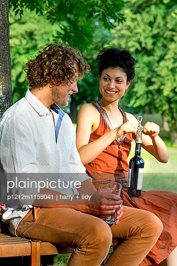 Paar beim Wein auf der runden Gartenbank - p1212m1159041 von harry + lidy