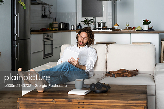 Relaxed man sitting on couch at home using tablet - p300m2143732 by Giorgio Fochesato