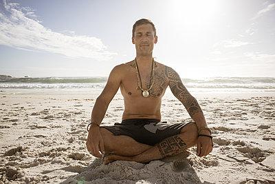 Mann meditiert auf dem Strand im Sonnenschein - p1640m2261024 von Holly & John