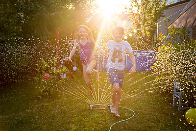 Brother and sister having fun with lawn sprinkler in the garden - p300m2023666 by Sandra Roesch