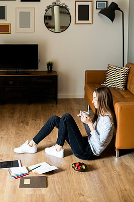 Relaxed young woman sitting on the floor at home drinking coffee - p300m2119921 by Giorgio Fochesato