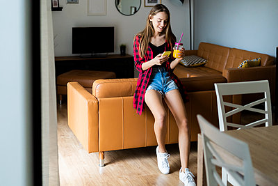 Happy young woman with cell phone and healthy drink at home - p300m2119932 by Giorgio Fochesato