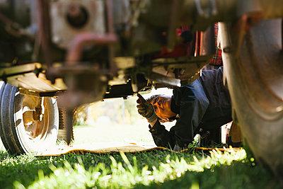 Woman repairing tractor - p312m2162002 by Matilda Holmqvist