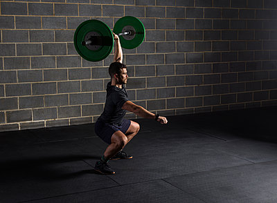 Man doing squats, lifting barbell in gym - p429m2098062 by Patrick Williamson Photography