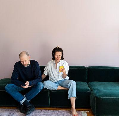 Pärchen mit Handy auf dem Sofa - p432m2175457 von mia takahara